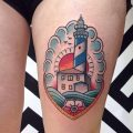 Traditional lighthouse tattoo on the thigh