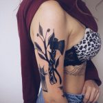Axe and branch tattoo
