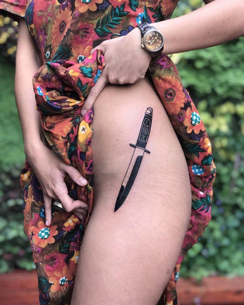 Black knife tattoo on the hip