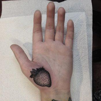 Black strawberry tattoo on the palm