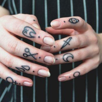 Black symbol tattoos on fingers