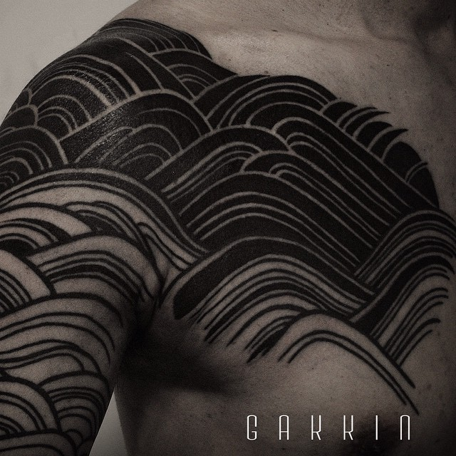 Black waves tattoo on the chest