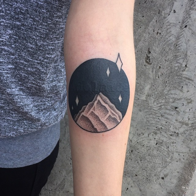 Circular mountain peak tattoo