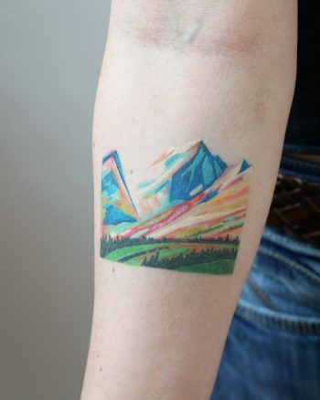 Colorful mountains tattoo on the forearm
