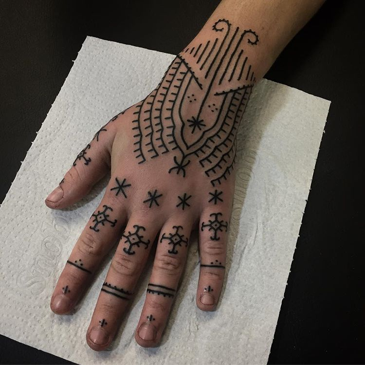 Cross and line tattoos on fingers