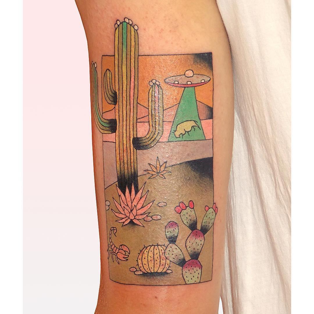 Desert landscape and alien abduction tattoo
