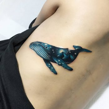 Double exposure whale and cosmic background tattoo