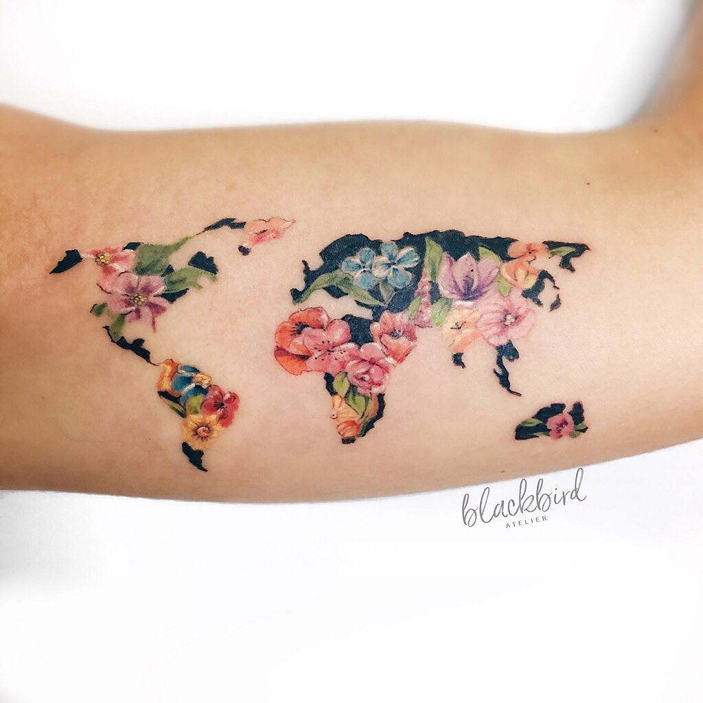 Floral world map tattoo on the bicep