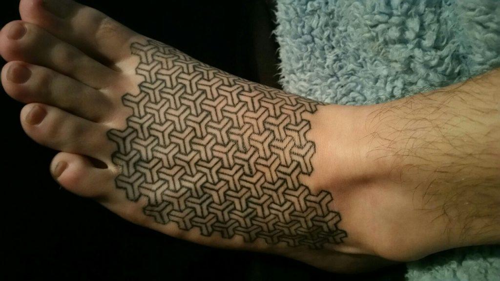 Geometric pattern tattoo on the left foot