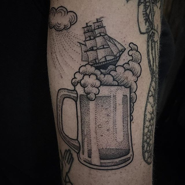 Glass of beer and a ship tattoo