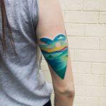 Heart shaped bluish landscape tattoo