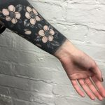 Negative space black flowers tattoo