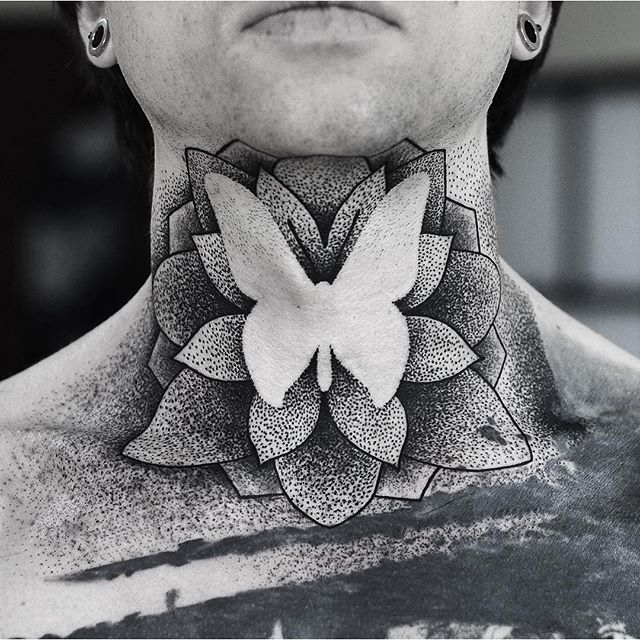 Negative space dotwork style lotus flower and butterfly tattoo