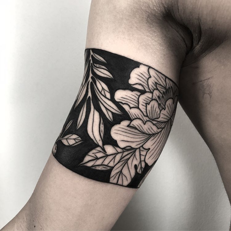 Negative space floral armband tattoo