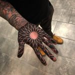 Negative space ornament tattoo on the palm