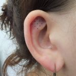 Nine dots tattoo on the ear