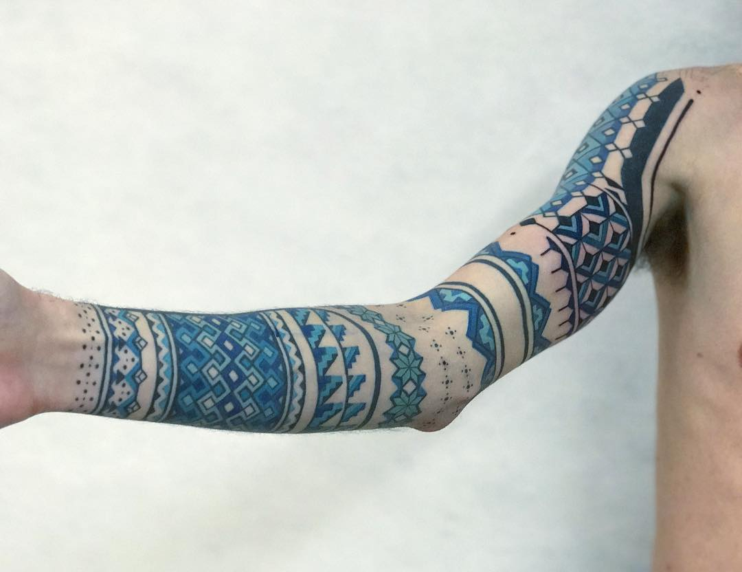 Ornamental blue sleeve tattoo