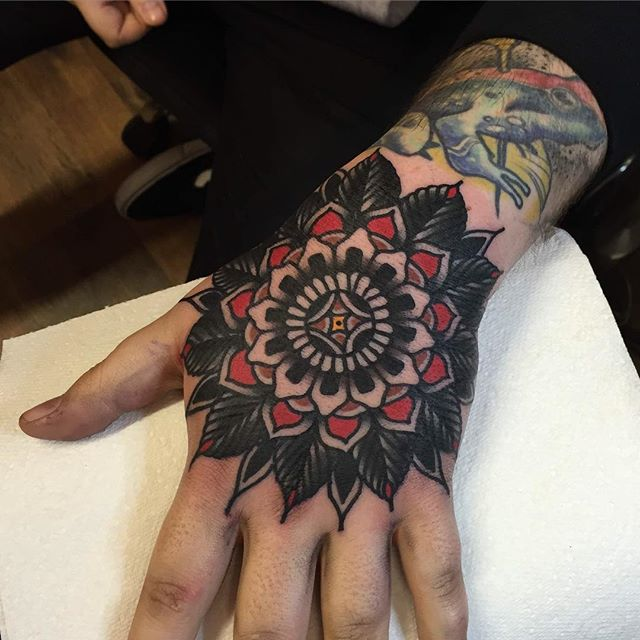Red and black mandala hand tattoo