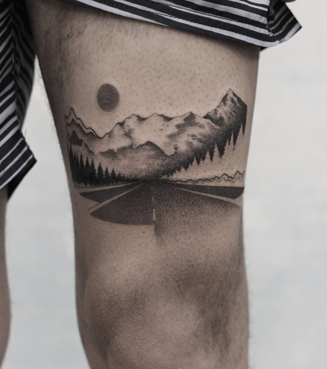 Road tattoo on the thigh