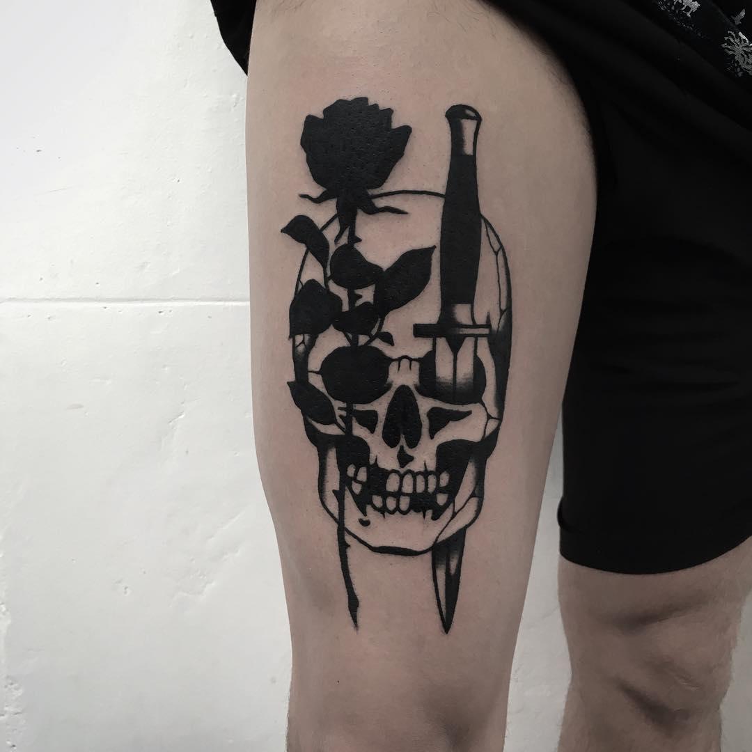 Rose and dagger stabbed skull tattoo