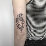 Simple flower tattoo on the back of the arm