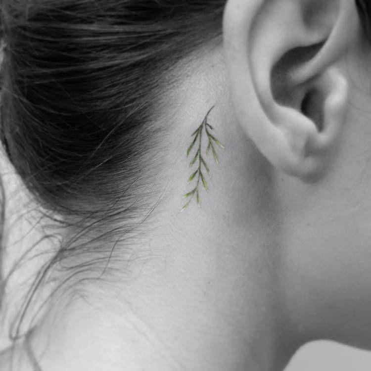 Small green twig tattoo behind the ear