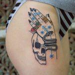 Snake handler's hand and skull tattoo