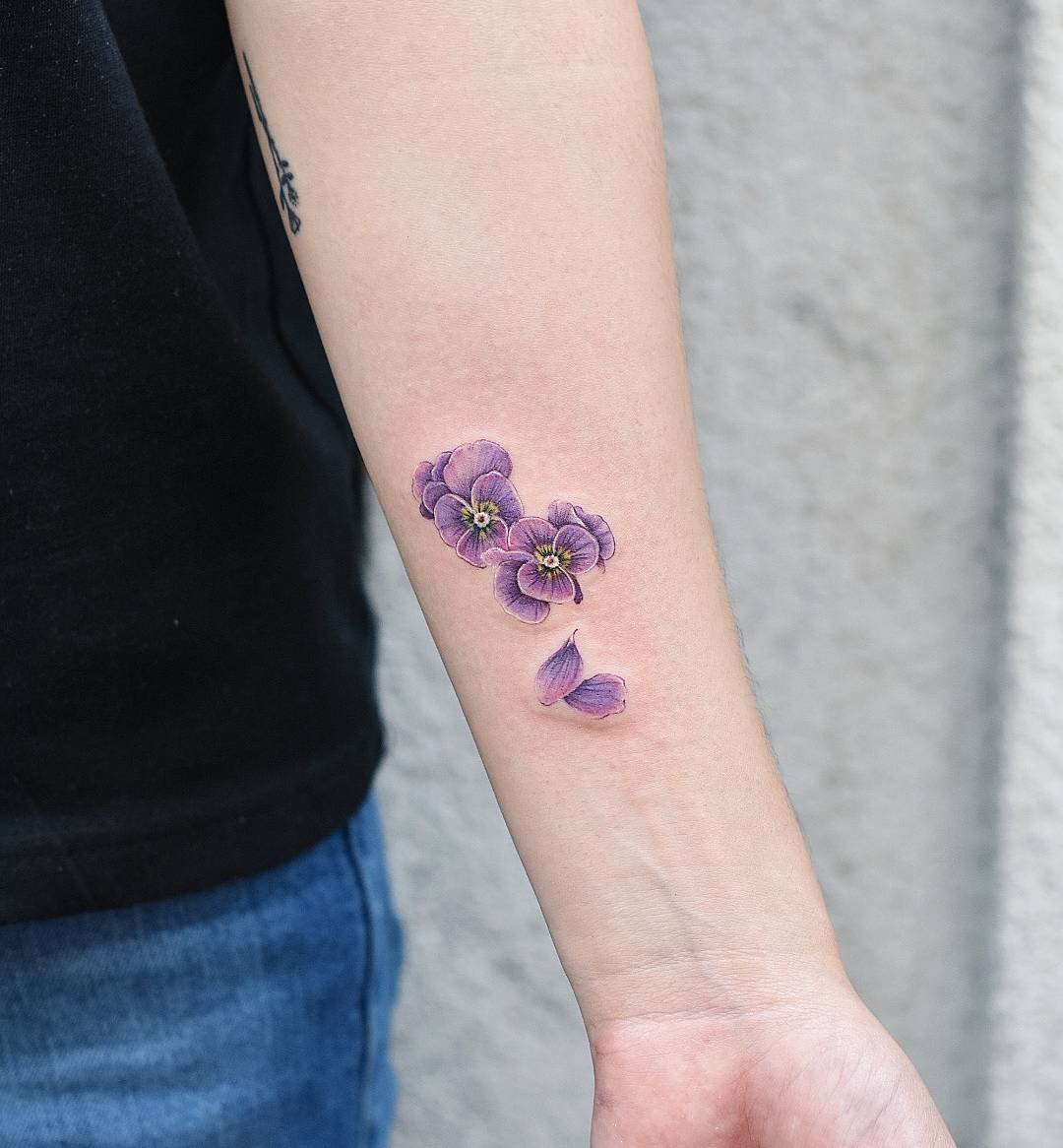 Tiny purple flowers tattoo on the wrist