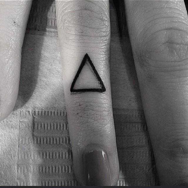 Tiny triangle tattoo on the finger