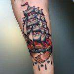 Traditional handshake and ship tattoo