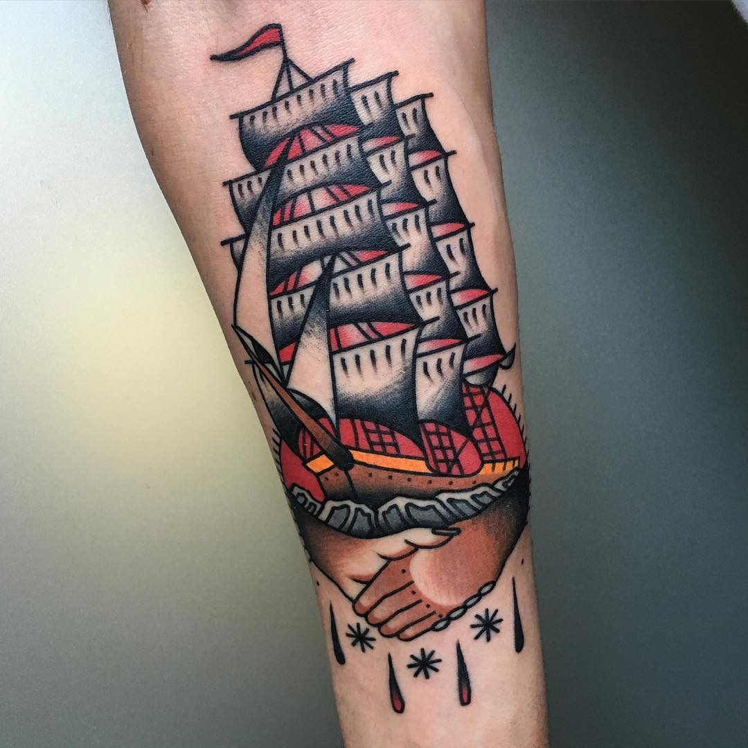 Traditional handshake and ship tattoo