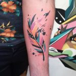 Watercolor feather tattoo on the forearm
