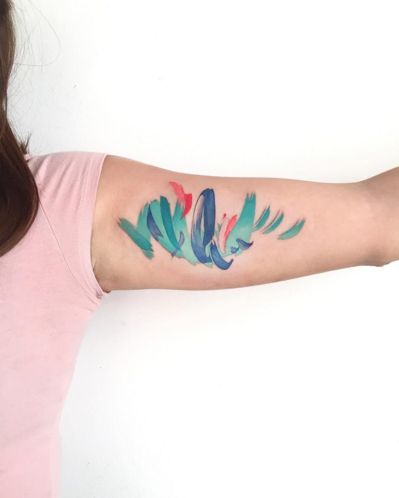 Abstract colorful tattoo on the bicep