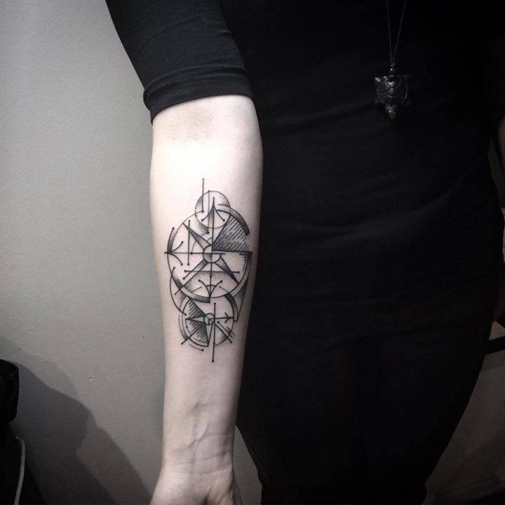 Abstract compass tattoo on the forearm