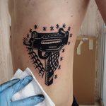 Black and grey uzi tattoo