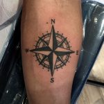 Black compass rose tattoo