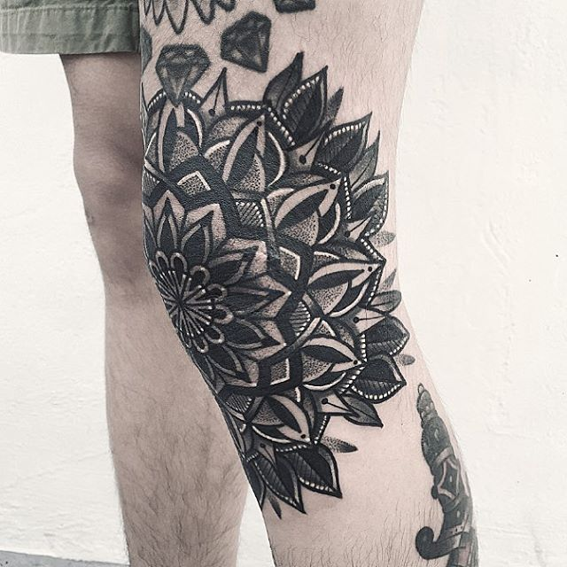 Black floral mandala tattoo on the knee