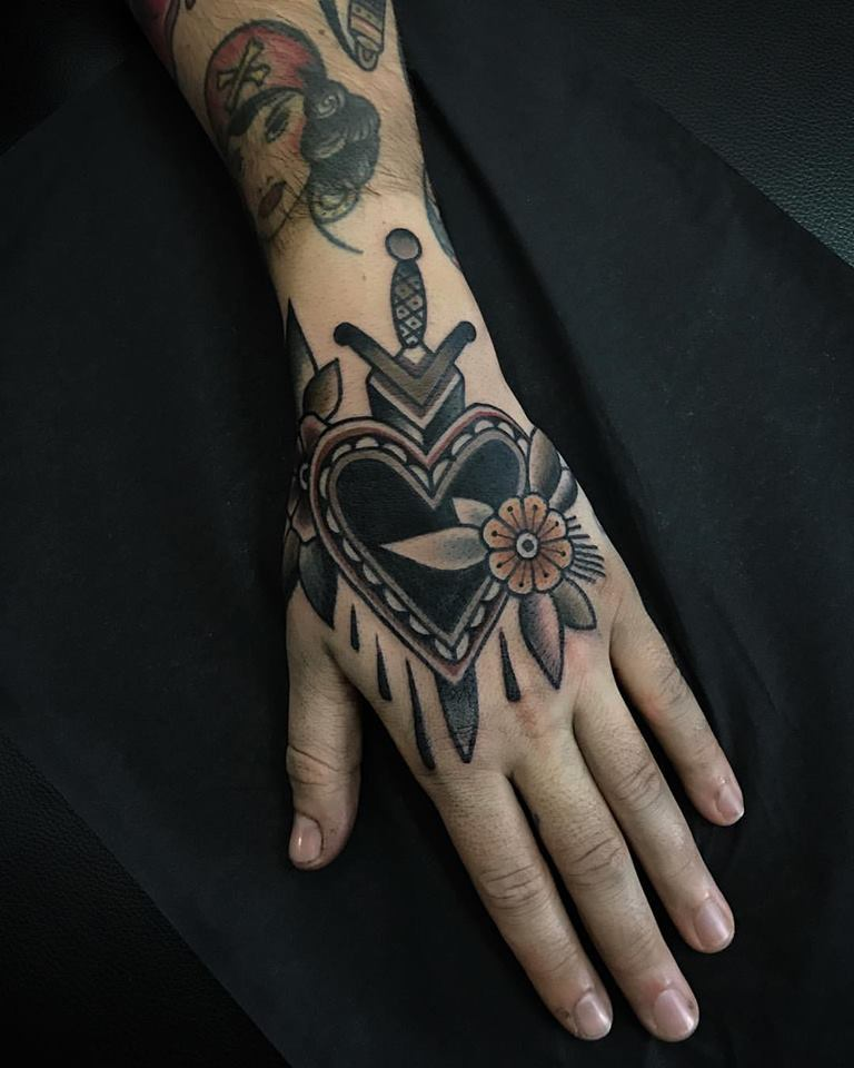 Black heart and dagger tattoo