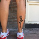 Black long rose tattoo on the right calf