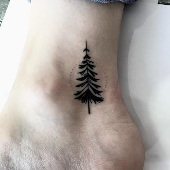 Black pine tree tattoo on the inner ankle