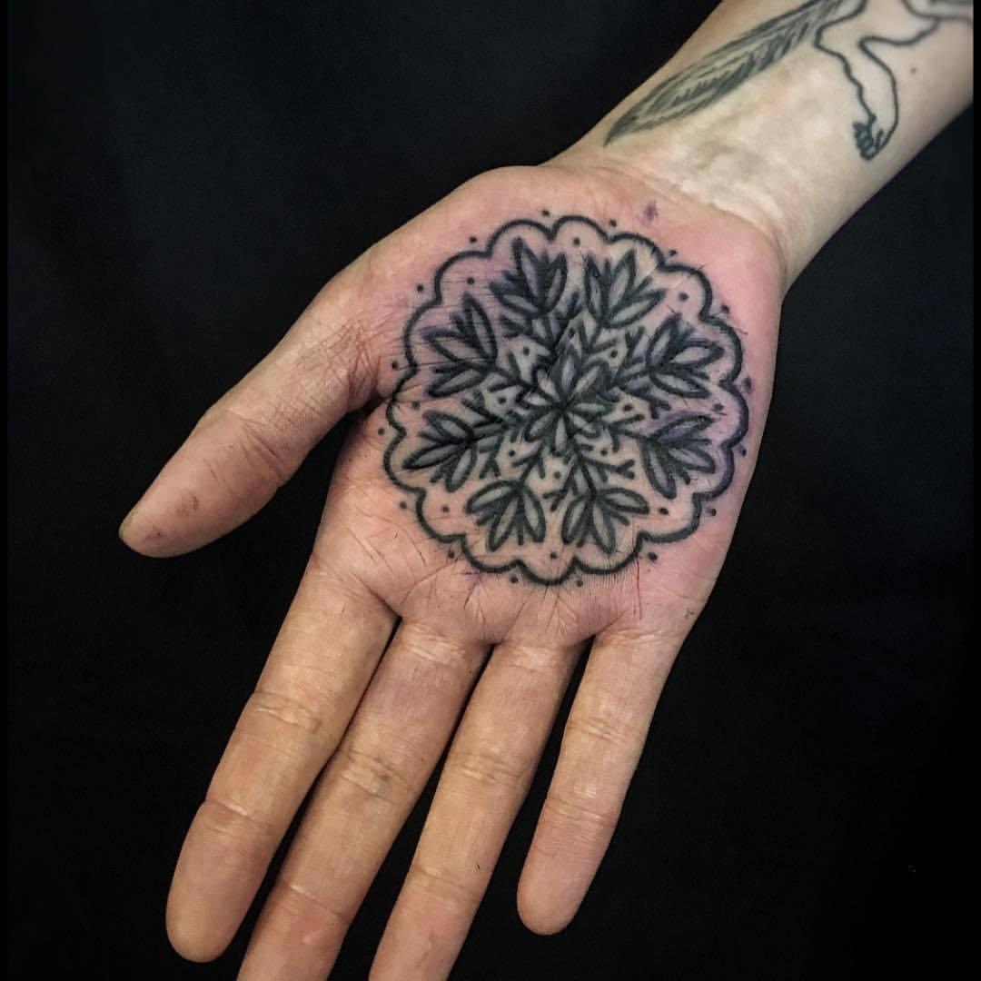 Black snowflake tattoo on the palm