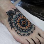 Blue and yellow mandala tattoo on the foot