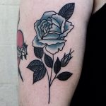 Blue rose tattoo on the bicep