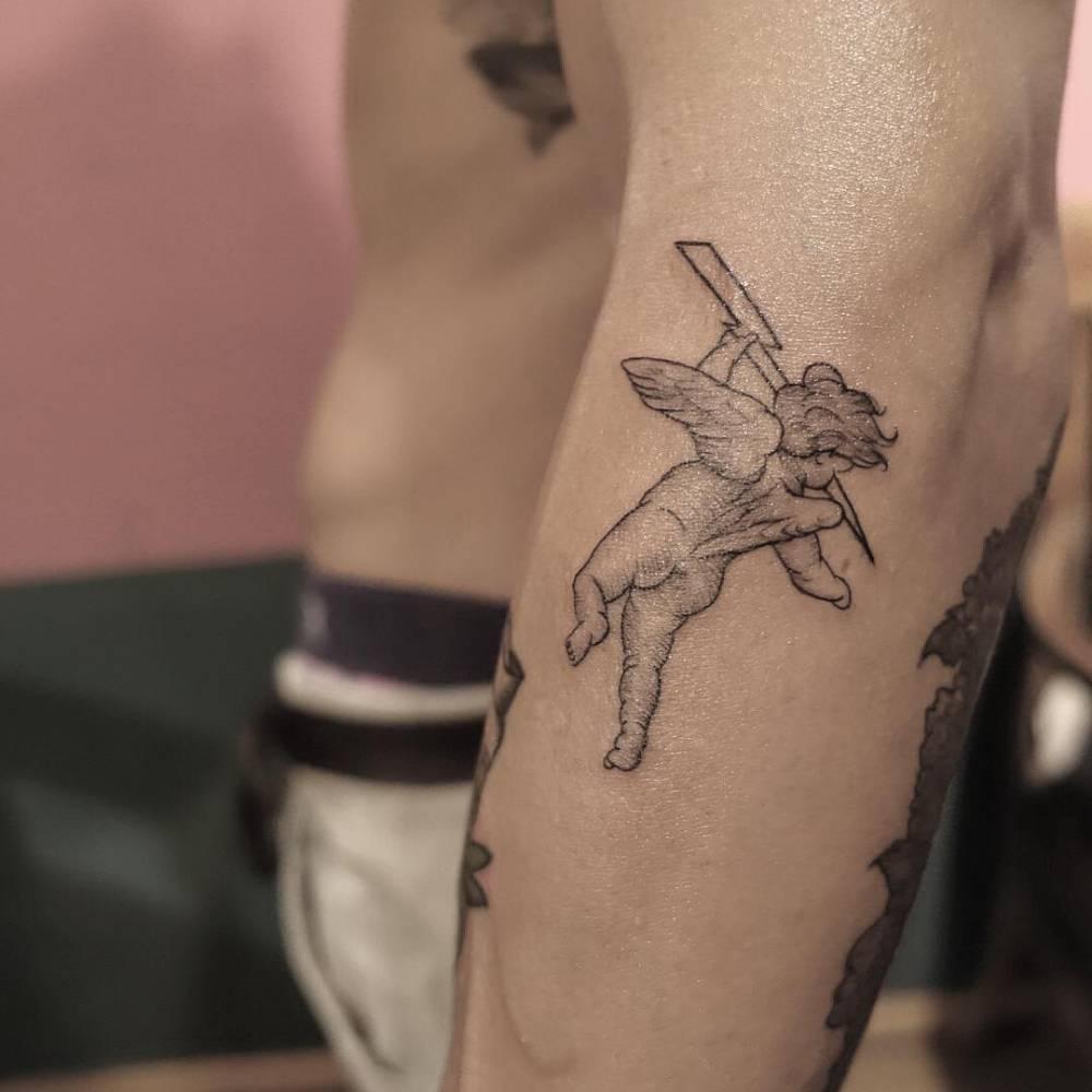 Cherub tattoo on the left forearm