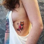 Colorful fox tattoo on the left ribcage