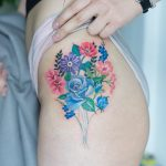 Colorful flower bouquet tattoo on the hip