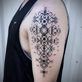 Geometric black tattoo on the left upper arm