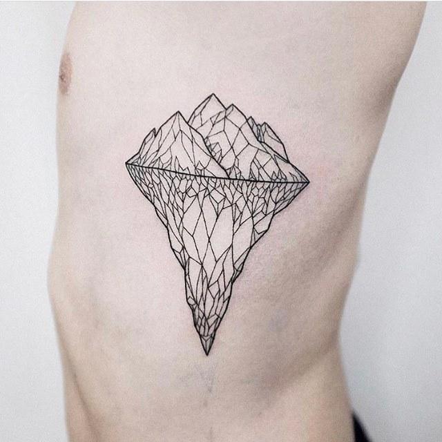 Geometric iceberg tattoo on the rib cage