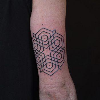 Geometric ornament tattoo above the elbow