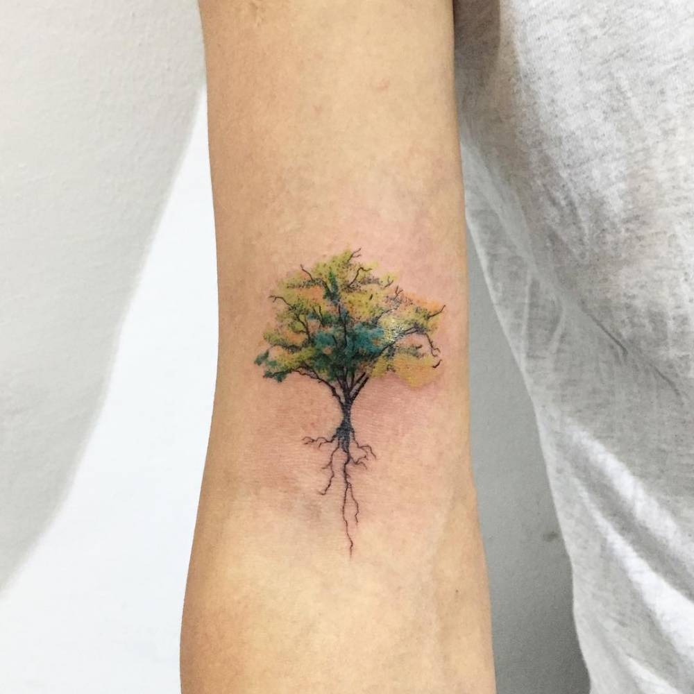 Green tree tattoo on the right arm